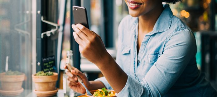 african american young woman eating while looking at phone