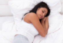 Young woman sleeping on a bed with white sheets and pillows