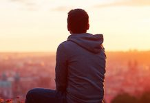 guy looking at sunset overlooking city