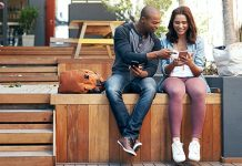 guy and girl sitting outside sharing phones