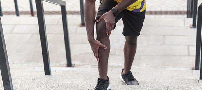 guy running up stairs holding knee