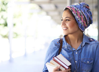 Young woman smiling while walking and carrying her books