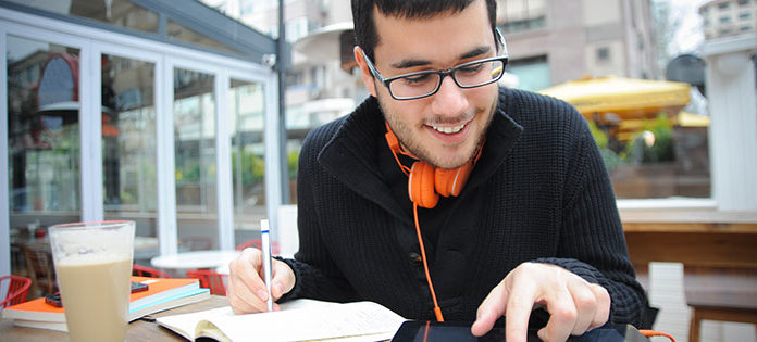 Guy taking notes and using an iPad