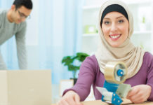 Female wearing hijab packing boxes with a friend