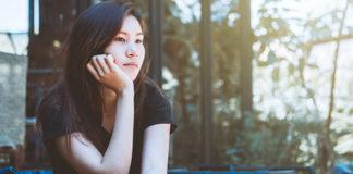 pensive asian young woman