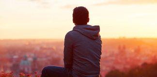 boy watching a sunset over city