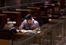 Student studying in library alone.