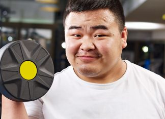 Happy, large Asian man working out in a gym