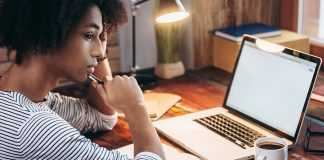 A young woman thinking while on her computer