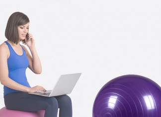 A girl sitting on a yoga ball on the computer