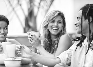 Three young people laughing over coffee