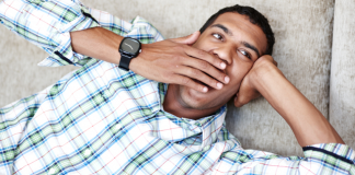 A young man laying down and yawning
