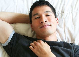 A young man smiling laying down on a bed