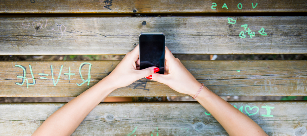 A young girl texting at a picnic table
