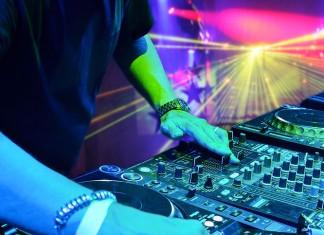 A DJ playing under lights