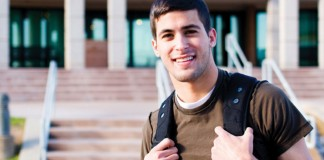 Young man standing in front of school with backpack, smiling