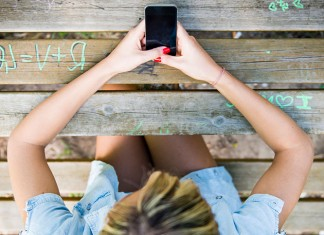 Girl sitting at a picnic table with her phone in her hands