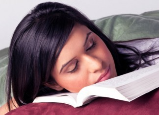 Young woman sleeping on her textbook