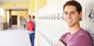 Young man standing in front of hallway locker